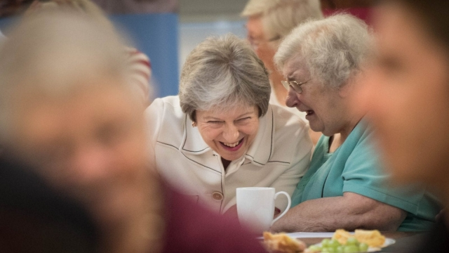 Theresa May talks with people attending a social group in Vauxhall Gardens Community Centre in London during the launch of the government's loneliness strategy last year.
