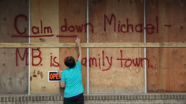 A woman sprays a message for the hurricane in Mexico Beach, Florida, as it approaches the coast (Photo: Getty)