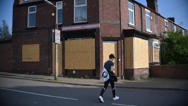 A young man passes a closed down corner shop in Cranklow, Rotherham (Getty Images)