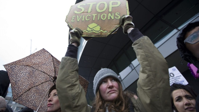 """A protester holds a placard that reads """"Stop Evictions"""" during a demonstration dubbed """"The March for Homes"""" calling for solutions to housing problems outside City Hall in London on January 31, 2015. (Getty Images)"""