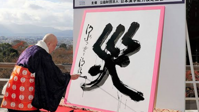 A temple master reveals the symbol of the year by painting it on live TV