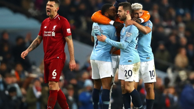 Manchester City players celebrate victory as Dejan Lovren of Liverpool looks dejected