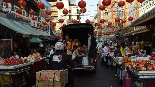 Vendors leave a market in a pick-up truck in Bangkok's Chinatown. (Photo: Getty)