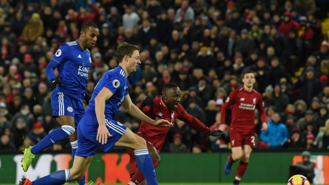 Naby Keita goes down in the Leicester penalty area under pressure from Ricardo Pereira