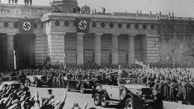 Adolf Hitler is saluted by the crowds as he makes his way to the great parade of troops in Vienna, Austria, 15th March 1938. Photo: Keystone/Hulton Archive/Getty