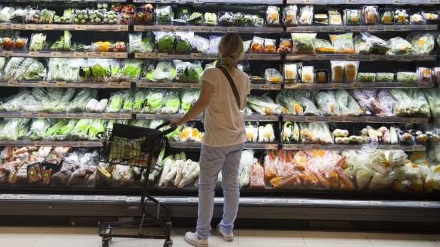 A shopper looks at a shelf of vegetables wrapped in plastics at a grocery store (Photo: Romeo Gacad/AFP/Getty Images)
