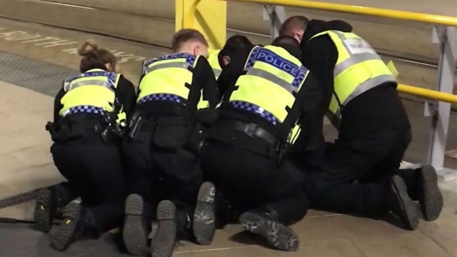 Article thumbnail: Police restraining a man after he stabbed three people at Victoria Station in Manchester. (Photo: Sam Clack/PA Wire)