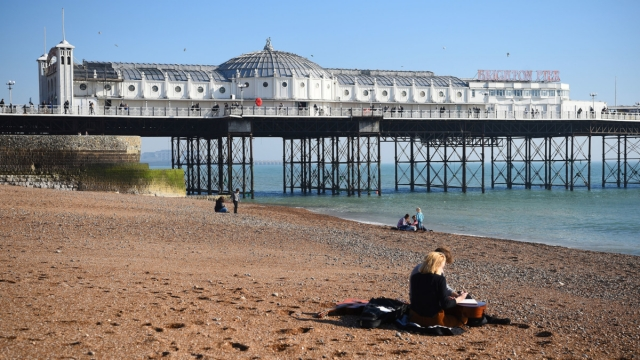 People sit on the beach next to the Brighton Palace Pier (Photo: PA)