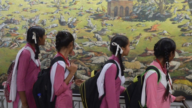 Indian school girls look at a painting of the martyrs during the 99th anniversary of the Jallianwala Bagh massacre (NARINDER NANU/AFP/Getty Images)