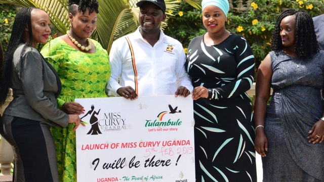 """Uganda's minister for Tourism Godfrey Kiwanda (C) poses next to participants during the launch of the Miss Curvy beauty contest in capital Kampala on February 5, 2019. - Female Ugandan activists on February 7, 2019, slammed a government campaign to use """"curvy women"""" as a tourism """"product"""" after Uganda's minister for Tourism Godfrey Kiwanda unveiled the campaign on February 6, 2019. """"We decided to use the unique beauty, the curves... to make this beauty a product to be marketed (...) to make it a tourist attraction,"""" Kiwanda told AFP. Part of the plan to market Ugandan women is a beauty pageant, Miss Curvy Uganda, to be held in June. Ugandan women were outraged at the proposal and have called for Kiwanda's resignation. Kiwanda, trying to stem the anger, insisted the campaign was not aimed at demeaning women. (Photo by STRINGER / AFP)STRINGER/AFP/Getty Images"""