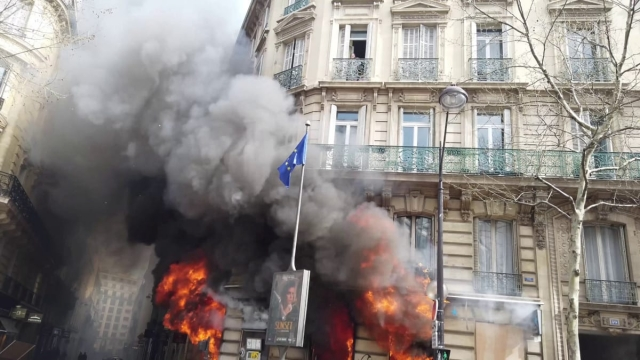This is the horrifying moment a mother holding a young baby screams for help on the second floor of a burning building in central Paris. See SWNS story SWOCfire. The terrifying footage shows a woman and her nine-month-old baby trapped directly above a raging fire, near the Champs-Elysées, Paris, on Saturday (March 16). Panicked bystanders can be seen pleading with the petrified woman to try to make an escape, as armed police and fire fighters desperately try to launch a rescue. The fire, at the local banking agency, Banque Tarneaud, is understood to have been started during the latest anti-government riot to have hit the city.
