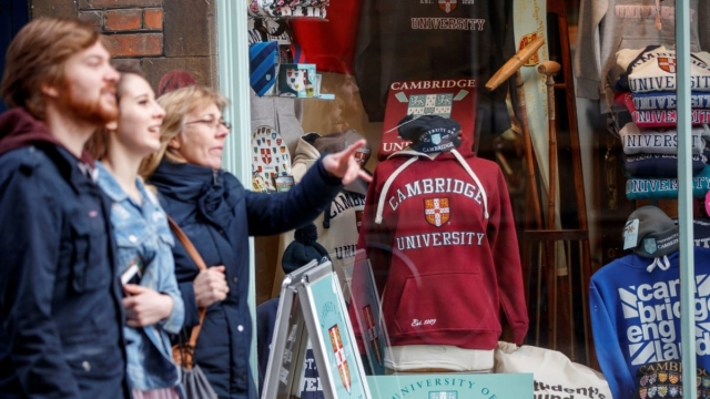 People walk past a Cambridge University souvenir shop (Photo: Tolga Akmen/AFP/Getty Images)