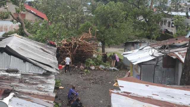 Article thumbnail: People stand by damaged houses and fallen tree in Comoros (Photo: Ibrahim YOUSSOUF / AFP)IBRAHIM YOUSSOUF/AFP/Getty Images