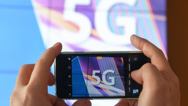 Article thumbnail: A journalist takes pictures of a projection screen prior to the start of Germany's auction for the construction of an ultra-fast 5G mobile network on March 19, 2019 at the German Federal Network Agency (BNA, Bundesnetzagentur) in Mainz, western Germany. - Germany launched the action as a transatlantic dispute rages over security concerns surrounding giant Chinese telecoms equipment maker Huawei. '5G' -- 'fifth generation' -- is the latest, high-speed generation of cellular mobile communications and Berlin will require winning bidders to offer 5G service to at least 98 percent of German households and along motorways and rail lines. (Photo by Arne Dedert / dpa / AFP) / Germany OUT (Photo credit should read ARNE DEDERT/AFP/Getty Images)
