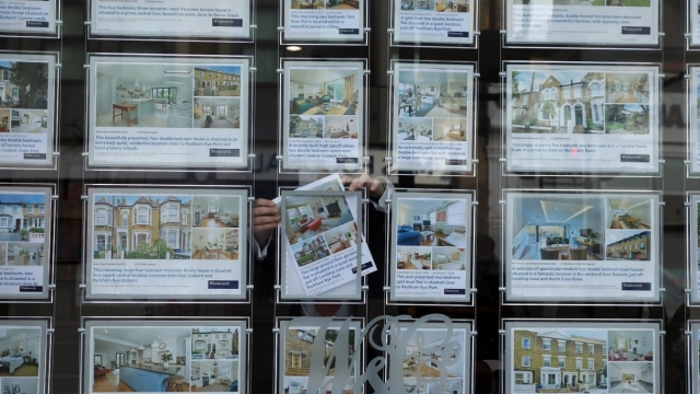 An Estate Agent poses inside the display window in London on 1 November 2017 (Getty Images)