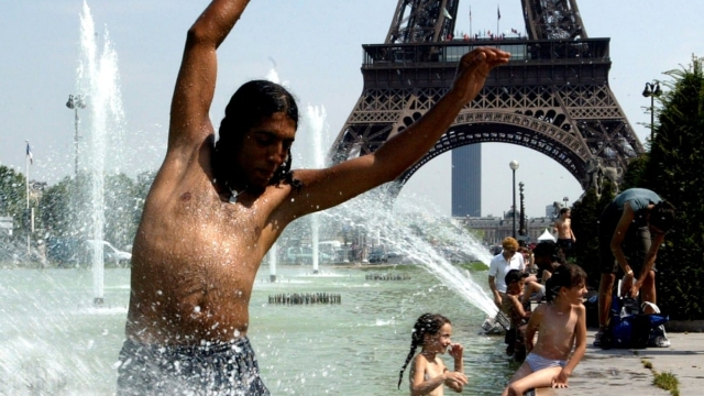 A tourist cools down in the fountains of the Trocadero near the Eiffel tower, July 15, 2003. Parisians are recalling the swelteringly hot summer of 2003 (Photo: REUTERS/Philippe Wojazer/File Photo)