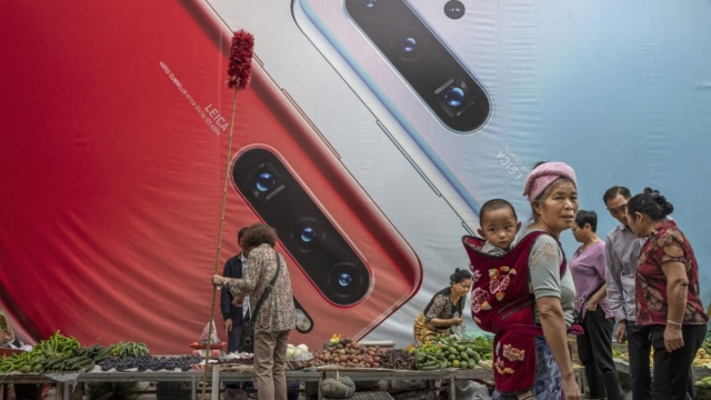 MANGSHI, CHINA - JUNE 1: A woman carries a child pasased a billboard advertising smartphones for China's Huawei Technologies Co., at a market on June 1, 2019 in Mangshi, Yunnan Province, southwestern China. (Photo by Kevin Frayer/Getty Images)