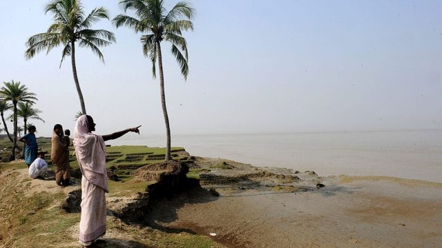 Madhuri Sardar points at the part of the river which submerged her family's farmland ten years ago on Ghoramara Island in the Sundarbans. Photo: Deshakalyan Chowdhury/ AFP/Getty