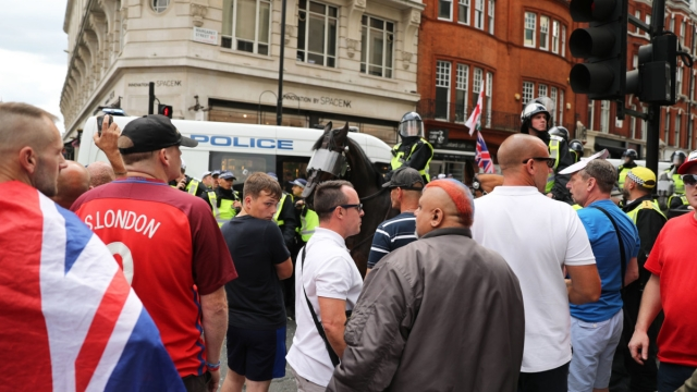 Tommy Robinson supporters are watched by police (Photo: Steve Parsons/PA Wire)