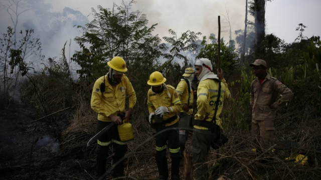 Firefighters rest briefly as they put out fires along the road to Jacunda National Forest