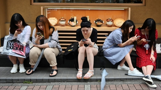 People use their smartphones while waiting in front of a restaurant in Tokyo's Ginza district on June 8, 2019. (Photo by Charly TRIBALLEAU / AFP) (Photo credit should read CHARLY TRIBALLEAU/AFP/Getty Images)