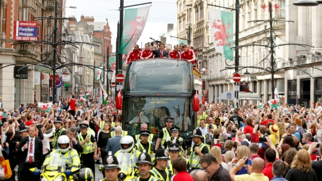 Wales players and manager Chris Coleman acknowledge the fans on a open top bus in Cardiff