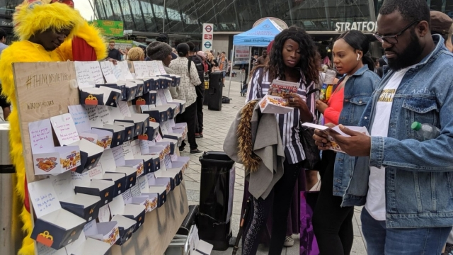 Members of the public writing inside chicken boxes outside Westfield Stratford. (PA)