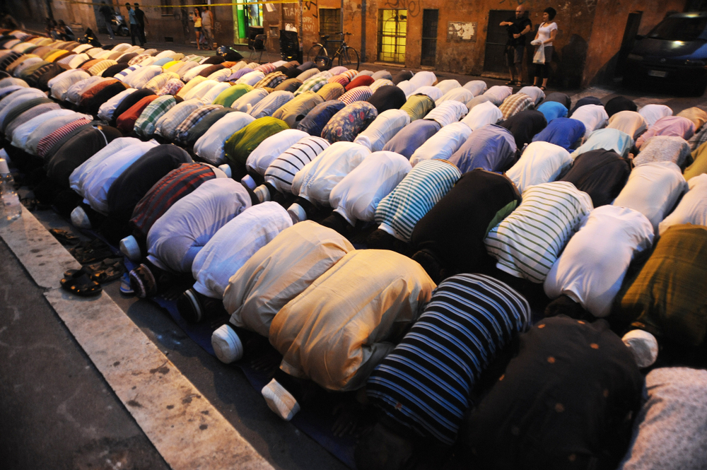 islamic young people during the prayer in a little mosque of rome