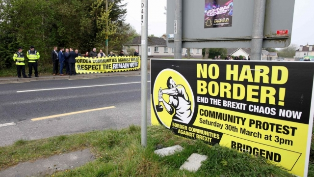 Protesters against Brexit and the possible imposition of any hard border between Northern Ireland and Ireland gather with a banner at the border