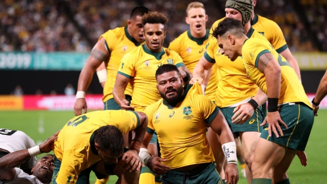 Tolu Latu of Australia is congratulated by his team mates after scoring against Fiji (Getty Images)