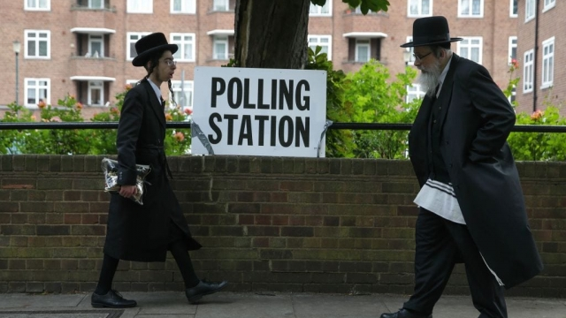 Orthodox Jewish men walk past a polling station sign in north London in 2017 during the general election