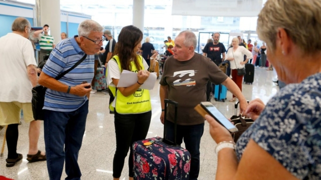Passengers talk to Civil Aviation Authority employee at Thomas Cook check-in points at Mallorca Airport