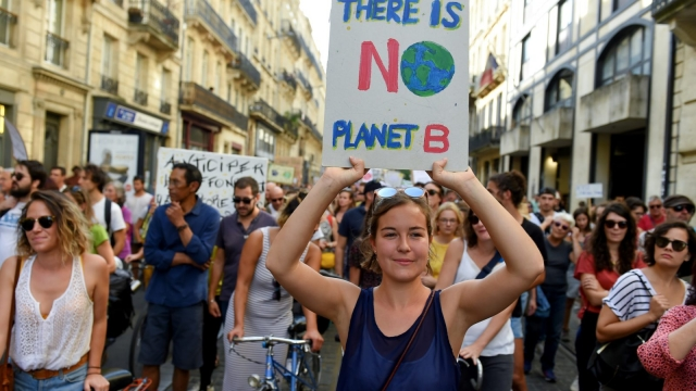 """A demonstrator holds a placard reading """"There is no planet B"""" during a march against climate change, in Bordeaux, southwestern France, on October 13, 2018. (Photo by NICOLAS TUCAT / AFP) (Photo credit should read NICOLAS TUCAT/AFP/Getty Images)"""