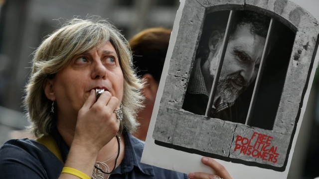 Article thumbnail: A woman holds placards depecting a picture of jailed Catalan separatist leader Jordi Cuixart in Barcelona amid street protests (