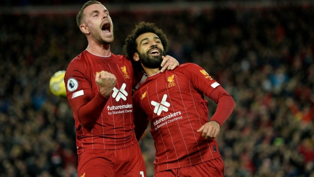 Liverpool's Egyptian midfielder Mohamed Salah celebrates with Jordan Henderson after scoring a penalty (AFP via Getty Images)