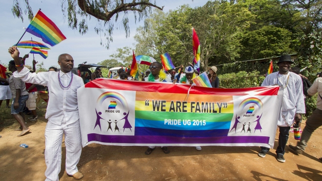 """People hold a banner reading """"We are Family"""" while waving rainbow flags as they take part in the Gay Pride parade in Entebbe on August 8, 2015. Ugandan activists gathered for a gay pride rally Photo: ISAAC KASAMANI/AFP/Getty Images)"""