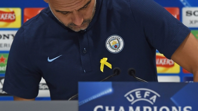 Manchester City's Spanish manager Pep Guardiola wearing a yellow ribbon pinned to his shirt to support imprisoned pro-independence politicians in his native Catalonia (AFP via Getty Images)