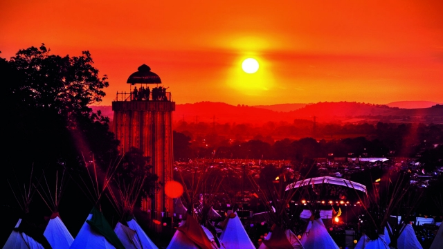 "A view at sunset of the teepee village overlooking the Park, Glastonbury Festival 2010. ""We built the Ribbon Tower because we wanted people to have a different perspective of the site, ideally one from the sky, because it looks so wonderful. People can come up and take in the amazing view"", says Emily Eavis. Photo: ©Barry Lewis"