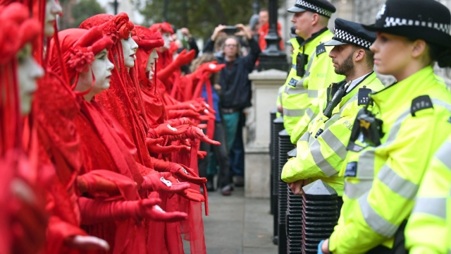 Protesters, dubbed the Red Rebels, outside the Cabinet Office on Whitehall, during an Extinction Rebellion (XR) protest in Westminster, London