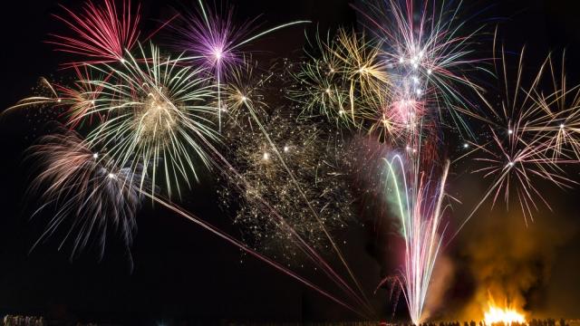 Fireworks in a dark sky, a bonfire beneath