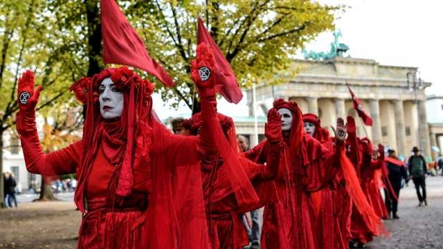 "A group of activists from the ""Red Rebel Brigade"" perform at the demonstration by climate change action group ""Extinction Rebellion"" (Photo: Britta Pedersen / dpa / AFP)"