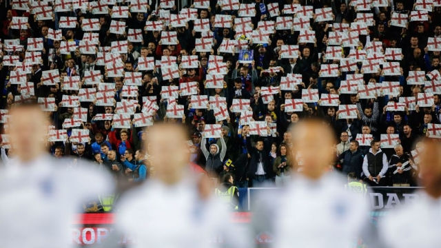 Article thumbnail: Kosovo fans hold up England flags as England's anthem 'God save the queen' is being played on 17 November 2019. (AFP via Getty Images)
