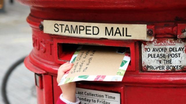 Child is posting a letter for Santa into traditional english postbox