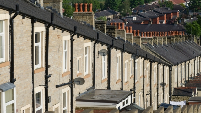 A typical row of Lancashire town stone facade built and slate roof covered terraced houses. Red chimney stacks top the buildings with the hills visible in the distance