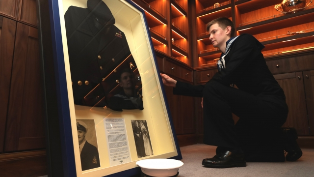 Able Seamn Seth Day, aged 17, of the HMS Prince of Wales, admires the uniform of Alf Woodhead. (Photo: Leading Photographer Joe Cater, Royal Navy)