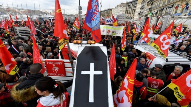 People wave the flags of French trade union General Confederation of Labour (CGT) and carry a mocked coffin as they take part in a demonstration to protest against the pension overhauls, in Marseille, southern France