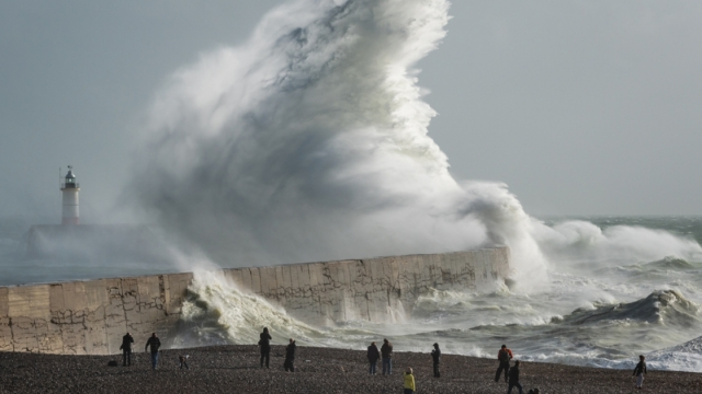 photographers and spectators on shingle beach watching Storm Brian huge waves break over harbour arm wall and lighthouse
