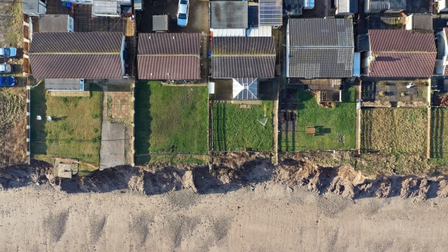 Article thumbnail: Houses on the coastline, where there are fears houses could be lost to coastal erosion. (Photo: Owen Humphreys/PA Wire)
