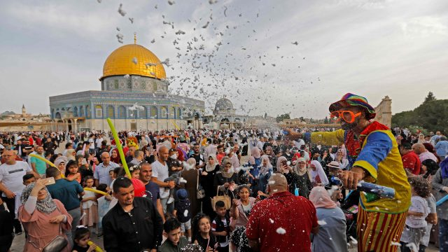 Article thumbnail: A clown entertains people as Palestinian Muslims perform the morning Eid al-Fitr prayer near the Dome of Rock mosque at the Al-Aqsa Mosque compound (Photo: Getty)