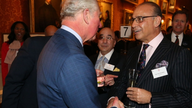 Article thumbnail: Dragon's Den star Theo Paphitis meeting Prince Charles last year. His retail companies Ryman and Robert Dyas have reported improved sales performance (Photo by Jonathan Brady - WPA Pool/Getty Images)